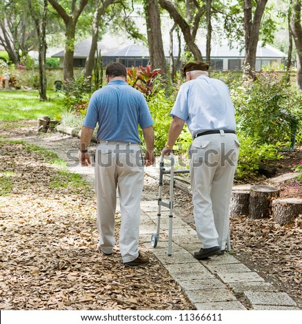 Father and son strolling through the garden together.  The father is in a walker. - stock photo