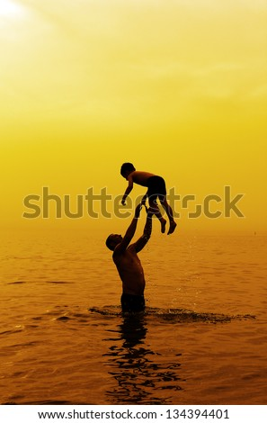father and son swimming in the sea at sunset - stock photo
