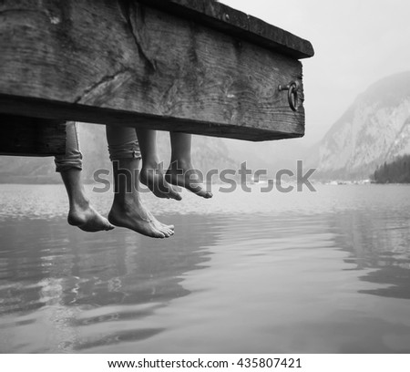 Father and son swung their legs from the wooden pier on mountain lake - stock photo