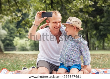 Father and son take a self picture with a phone  - stock photo