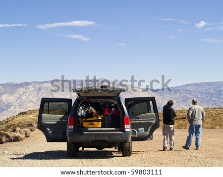 Father and son taking a break and enjoying the view during their road trip - stock photo