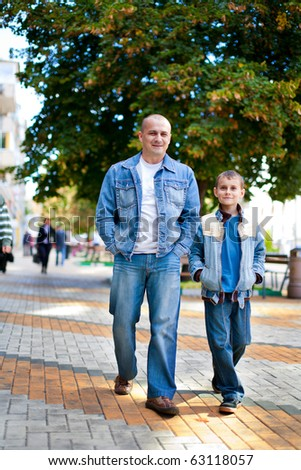 Father and son taking a walk outdoor in a park - stock photo