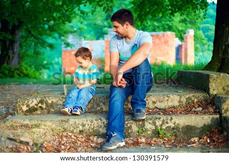 father and son talk, while sitting on old stairs among trees - stock photo