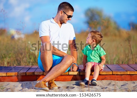 father and son talking, summer outdoor - stock photo