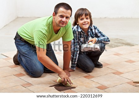 Father and son testing the color of joint on ceramic floor tiling - stock photo