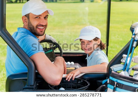 Father and son ? the best team. Cheerful young man and his son looking at camera while sitting in golf cart  - stock photo