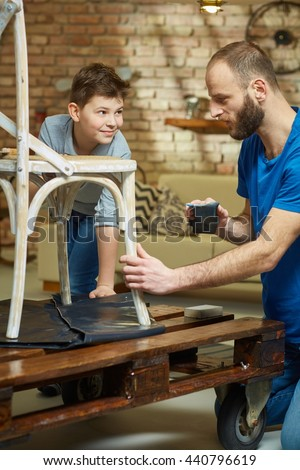 father and son tinkering at home, renewing chair. - stock photo