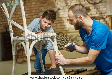 Father and son tinkering at home, renewing chair, polishing. - stock photo