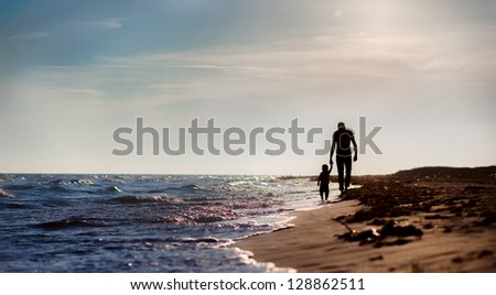 father and son to the sea at sunset - stock photo