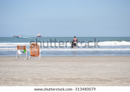 Father and son together at beach holding hands - stock photo