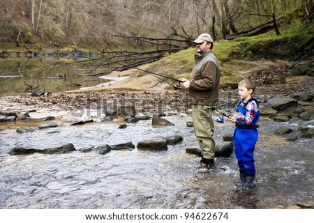 Father and son together catching trout in the river - stock photo