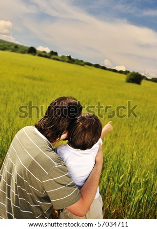 Father and son together in nature looking into the future - stock photo