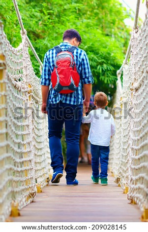 father and son traveling by suspension bridge - stock photo