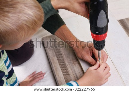 Father and son use drill. Boy helping his dad with building work at home.  Family concept