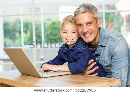 Father and son using laptop at home - stock photo