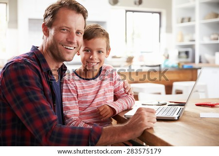Father and son using laptop computer at home - stock photo