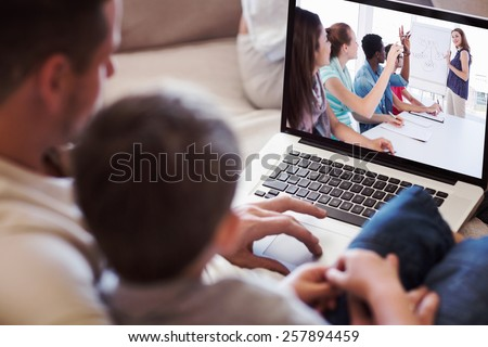 Father and son using laptop in house against casual business people in office at presentation - stock photo