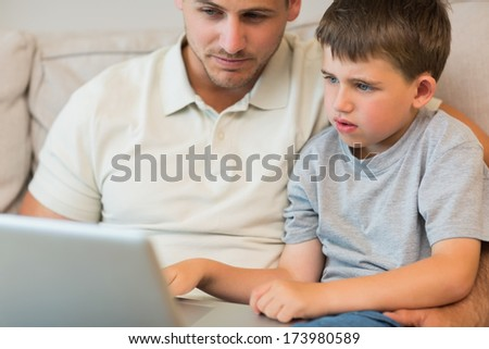 Father and son using laptop on sofa at home - stock photo