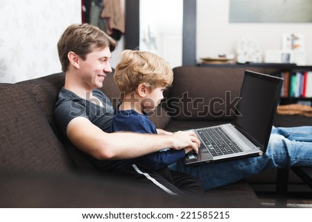 Father and son using laptop on sofa in house  - stock photo