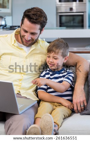 Father and son using laptop on the couch at home in the living room