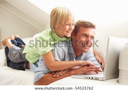 Father And Son Using Laptop Relaxing Sitting On Sofa At Home - stock photo