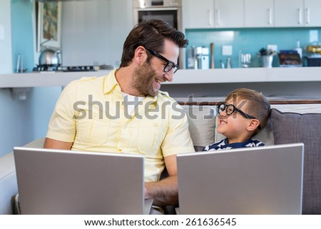 Father and son using laptops on the couch at home in the living room - stock photo