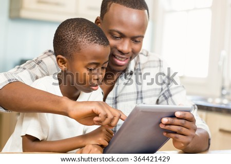 Father and son using tablet together in the kitchen - stock photo