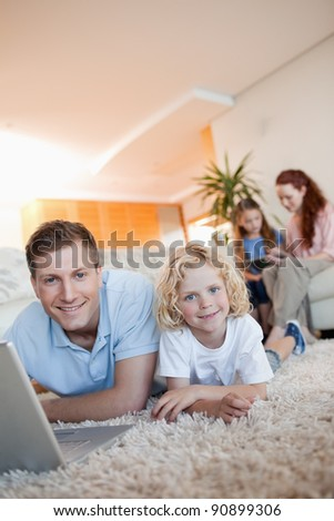 Father and son using the internet together on the floor - stock photo
