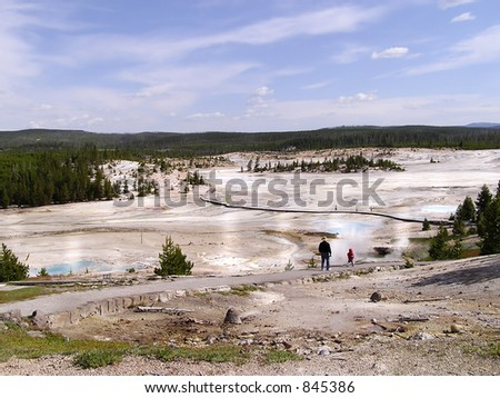 Father and son visiting the geysers of Yellowstone park - stock photo