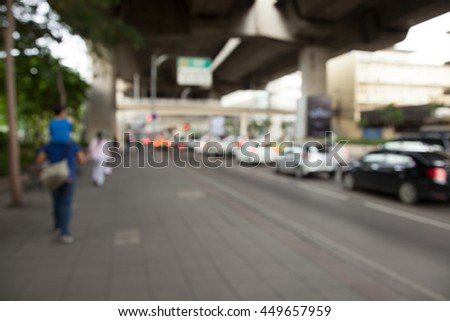 Father and son walking along a footpath in a traffic jam, Blur - stock photo