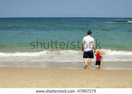 Father and Son Walking and Playing on the Beach - stock photo