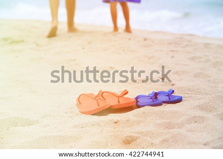 father and son walking at beach, flip flops on sand