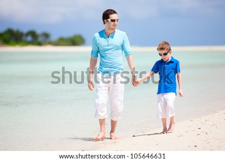 Father and son walking at tropical beach