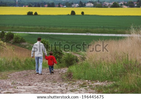 Father and son, walking in a field - stock photo