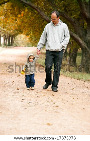 father and son walking in park - stock photo