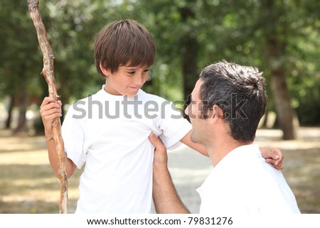 father and son walking in the park - stock photo
