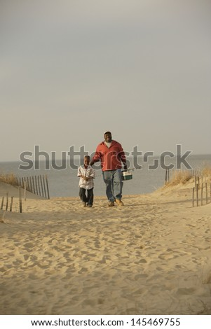 Father and son walking on beach with fishing gear - stock photo