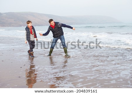 Father And Son Walking On Winter Beach And Throwing Stones