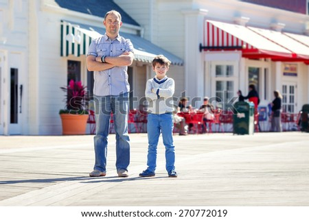Father and son walking outdoors in city during his summer vacation - stock photo
