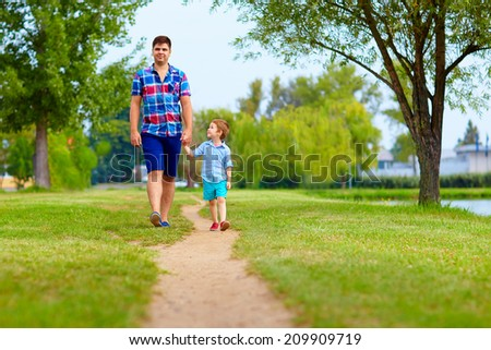 father and son walking together in park - stock photo