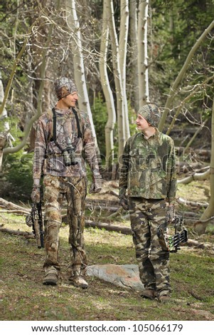 father and son walking together outdoors with archery hunting gear - stock photo