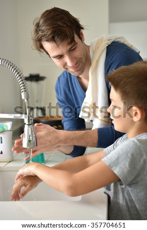 Father and son washing hands in kitchen