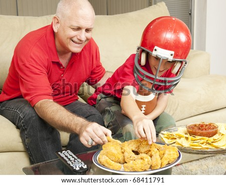 Father and son watching football together and eating snacks. - stock photo