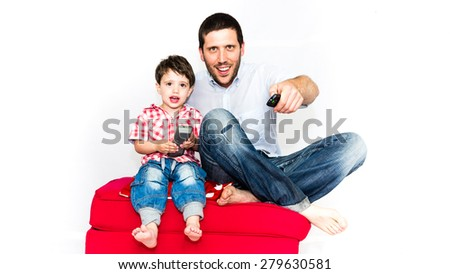 Father and son watching tv together on a red sofa - isolated on white background - stock photo