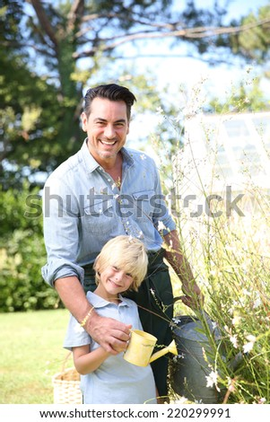 Father and son watering plants in garden