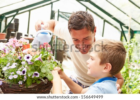 Father And Son Watering Plants In Greenhouse - stock photo