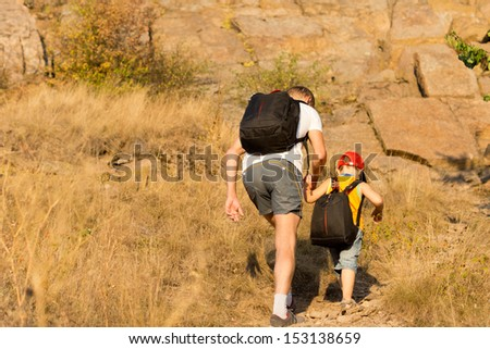 Father and son wearing backpacks hiking on a mountain holding hands to prevent the young boy from losing his footing