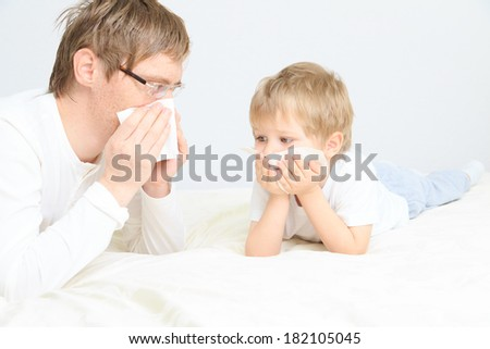 father and son wiping nose, illness - stock photo