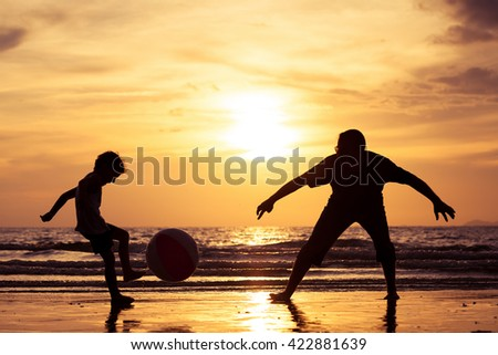 Father and son with ball playing soccer on the beach at the sunset time. Concept of friendly family. - stock photo