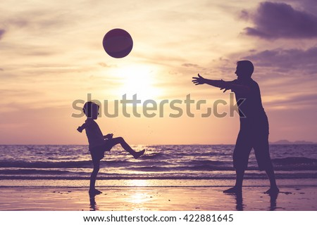 Father and son with ball playing soccer on the beach at the sunset time. Concept of friendly family.